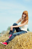 Happy smiling young girl sitting on a hay Stock Images