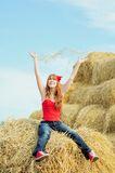 Happy smiling young girl sitting on a hay Royalty Free Stock Photo