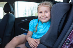 Happy smiling young girl sitting in infant restraint seat. In car Stock Images