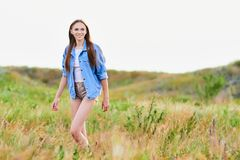 Happy young girl wearing blue jeans jacket in the field. Happy smiling young girl wearing blue jeans jacket and shorts is standing in the field stock photos