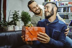 Happy smiling young handsome gay couple in love looking at each other celebrating and giving gift royalty free stock photo