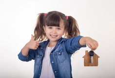 Child holding house keys on house shaped keychain like Real Estate Agent and showing thumbs up. stock images