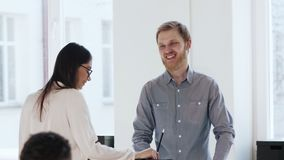 Happy smiling young male business manager talking to brunette colleague woman standing at trendy loft office table.