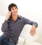 Happy smiling young man. Sitting on the leather sofa and talking on mobile phone Royalty Free Stock Image