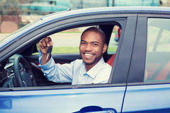 Happy, smiling, young man, buyer sitting in his new blue car showing keys Royalty Free Stock Image