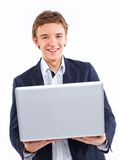 Happy smiling young man with computer laptop. Happy smiling young man watching and working on computer laptop at home Royalty Free Stock Image