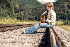 Happy smiling young man with guitar sitting on railway Stock Photography