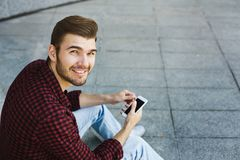Smiling young man using his phone outdoors. Happy smiling young man holding smartphone in his hand, having a rest in the university campus outdoors. Technology Royalty Free Stock Image