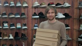 Happy smiling young man with new sneaker shoes in a shoe store, extreme sports shopping. Happy smiling young man trying on new winter shoes in a shoe store stock video