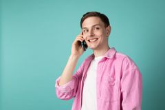 Happy smiling young man in pink shirt talking on mobile phone stock photography