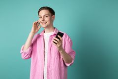 Happy smiling young man in pink shirt talking on mobile phone using wireless headphones royalty free stock photo