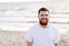 Happy smiling young man with red beard on beach Stock Photos