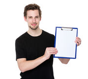 Happy smiling young man showing blank clipboard Royalty Free Stock Photos