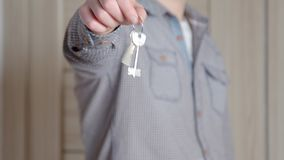 Happy smiling young man showing a pair of keys of their new house stock video