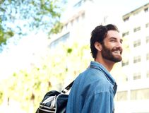 Happy smiling young man standing outdoors with travel bag Royalty Free Stock Photo