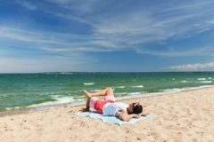 Happy smiling young man sunbathing on beach towel. Summer holidays and people concept - happy smiling young man sunbathing on beach towel Stock Photos
