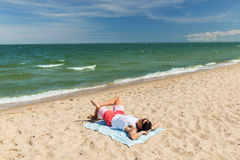 Happy smiling young man sunbathing on beach towel Stock Photo