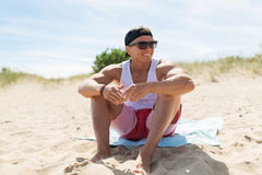 Happy smiling young man sunbathing on beach towel Stock Photography
