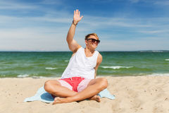 Happy smiling young man sunbathing on beach towel Royalty Free Stock Image