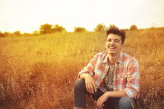 Happy smiling young man on a sunny autumn day. Portrait of a happy smiling laughing guy wearing a casual shirt sitting on yellow grass on a sunny autumn day stock image
