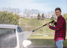 Happy smiling young man washing his car at pressure car wash Royalty Free Stock Photo