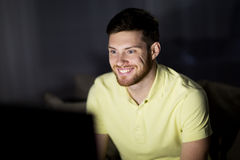 Happy smiling young man watching tv at night. People, mass media, television and entertainment concept - happy smiling young man watching tv at night at home Stock Photography