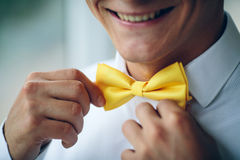Happy smiling young man in a wedding costume and yellow butterfly royalty free stock photo