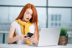 Happy redhead girl send an sms message to friend while working at modern office stock image