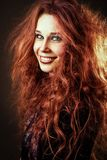 Happy smiling young redhead woman with long curly hair. Studio portrait royalty free stock images
