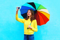 Happy smiling young woman with autumn colorful umbrella taking photo makes self portrait on smartphone over colorful blue Royalty Free Stock Images