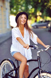 Happy smiling young woman on a bicycle Royalty Free Stock Image