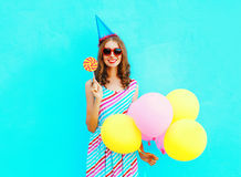 Happy smiling young woman in a birthday cap with an air colorful balloons and a lollipop on stick over a blue Royalty Free Stock Image