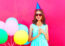 Happy smiling young woman in a birthday cap with an air colorful balloons and lollipop on stick over pink background Stock Photography
