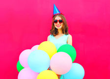Happy smiling young woman in a birthday cap with an air colorful balloons over pink background Royalty Free Stock Image