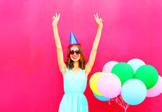 Happy smiling young woman in a birthday cap having fun on an air colorful balloons pink background Royalty Free Stock Images