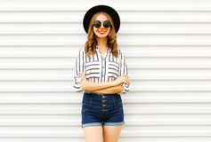 Happy smiling young woman in black round hat, shorts, white striped shirt posing on white wall. Background royalty free stock image