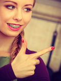 Happy smiling young woman with braces pointing Stock Photo