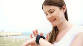 Woman using smartwatch on beach alone. Female chatting with friends via smart watch in slow motion. Happy smiling young woman browsing on smartwatch on beach stock footage