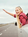 Happy smiling young woman in car window Stock Photos
