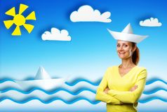 Happy smiling young woman on cartoon background. Smiling young pretty woman on sea cartoon background with paper hat Stock Images