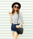 Happy smiling young woman with coffee cup in black round hat, shorts, white striped shirt on white wall. Background royalty free stock images