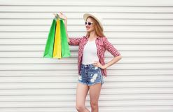 Happy smiling young woman with colorful shopping bags in summer round straw hat, checkered shirt, shorts on white wall royalty free stock photos