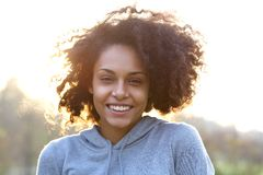 Happy smiling young woman with curly hair. Close up portrait of a happy smiling young woman with curly hair royalty free stock images