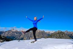 Happy smiling young woman dancing and jumping with joy in mountains. stock photos