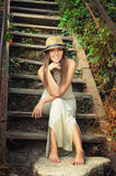 Happy smiling young woman dressed in hat and white long dress sitting barefoot on a vintage wooden stairs. Royalty Free Stock Photos