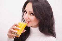 Happy smiling young woman drinking orange juice Royalty Free Stock Image