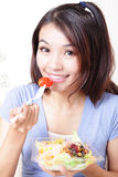 Happy smiling young woman eat salad Royalty Free Stock Images