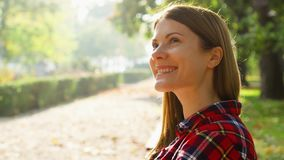 Happy Smiling Young Woman Enjoying Nature. Sitting on bench in green park. Freedom loneliness concept. Close up of happy Smiling Young Woman enjoying Nature stock footage