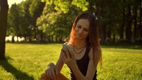 Happy smiling young woman enjoying nature and sunrise. Sitting on bench in green summer park using mobile. stock video