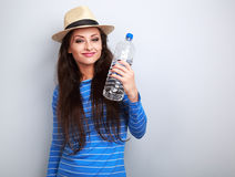 Happy smiling young woman holding bottle of pure water on blue b. Ackground Royalty Free Stock Photography
